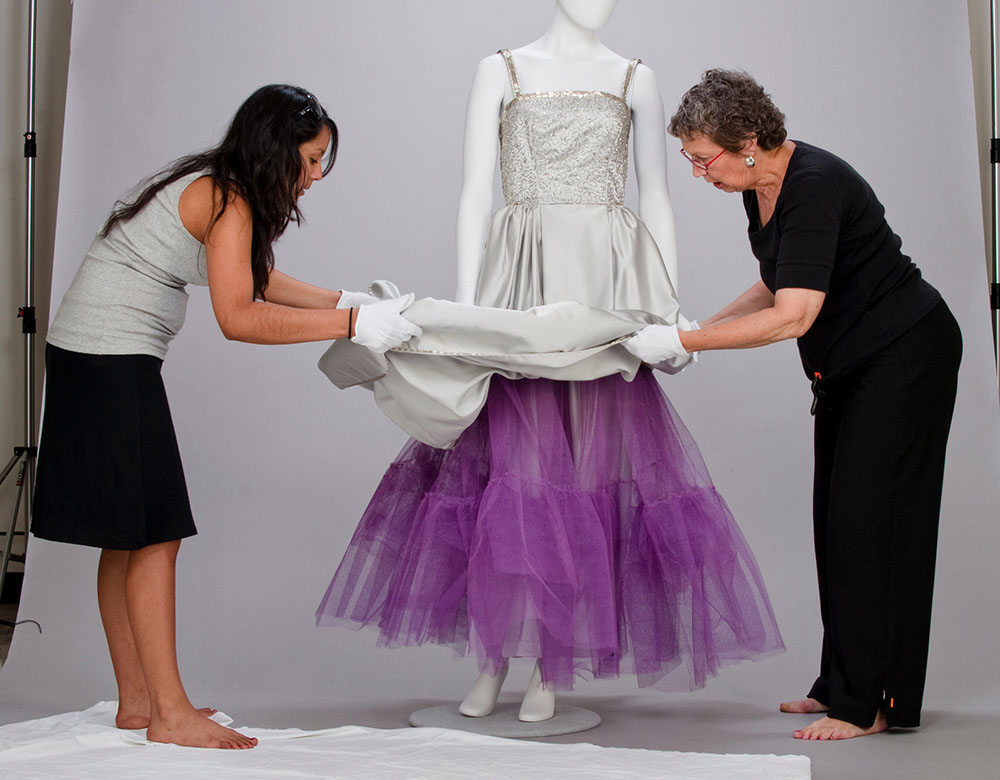 two women dressing a mannequin. Click to view the detail of this image