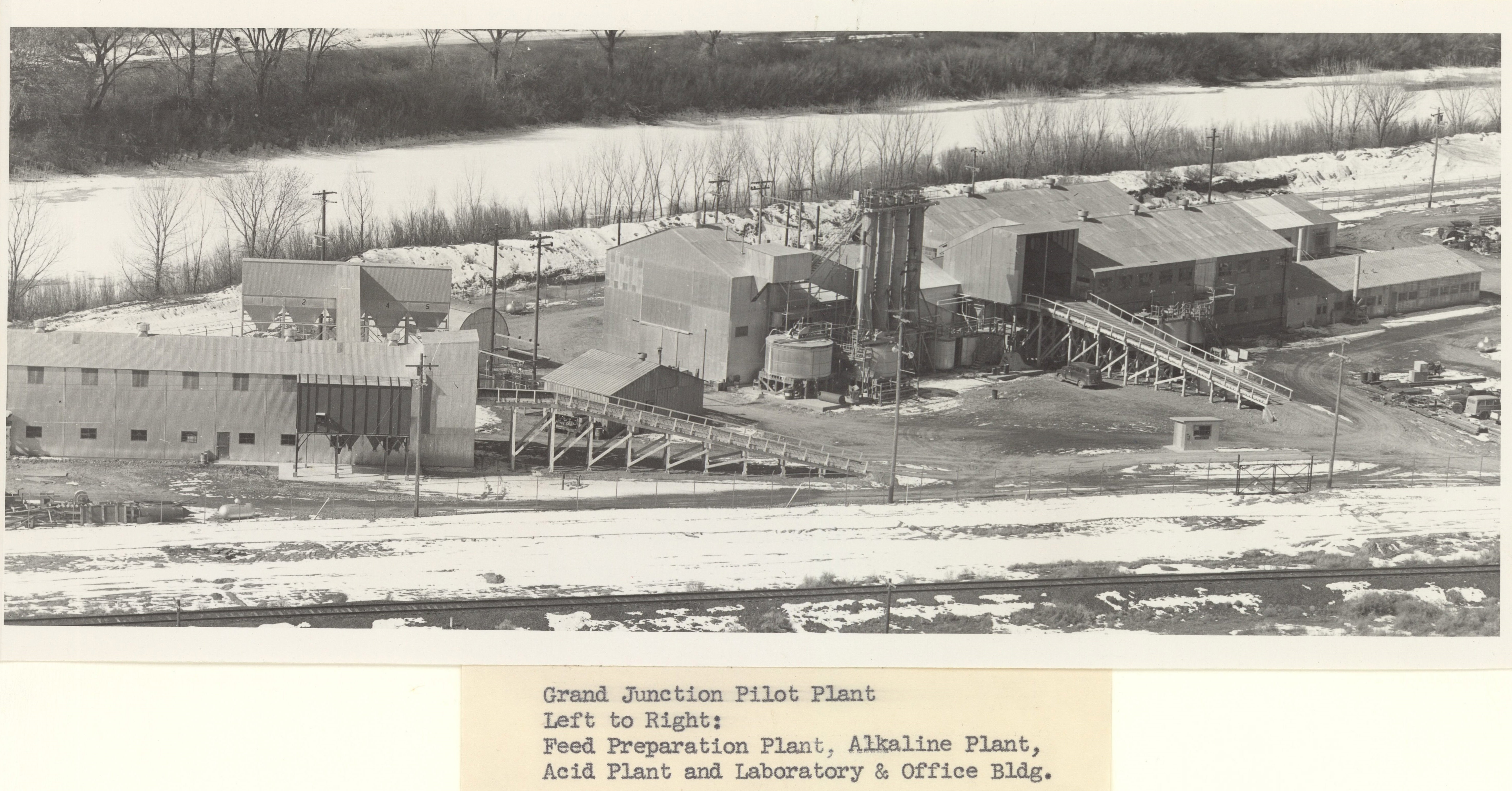 Black and white image of industrial facility constructed from corrugated metal with a frozen, snow-covered river near the top of the frame and a railroad track in the foreground, surrounded by patchy snow. A hand-typed caption reads: Grand Junction Pilot Plant. Left to right: Feed Preparation Plant, Alkaline Plant, Acid Plant and Laboratory & Office Bldg.